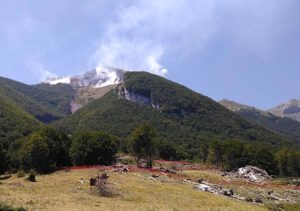 I resti dell'hotel Rigopiano e sullo sfondo l'incendio